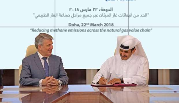 Al-Kaabi signs the 'Guiding Principles' document as van Beurden looks on at a ceremony in Doha on Th
