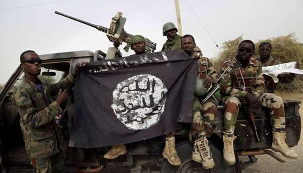 Nigerian soldiers hold up a Boko Haram flag that they had seized in the recently retaken town of Dam