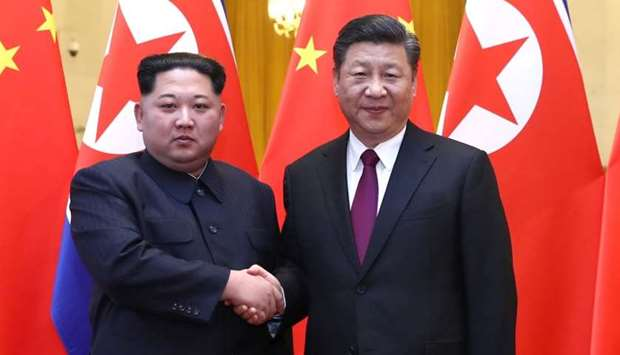 North Korean leader Kim Jong Un and Chinese President Xi Jinping shake hands at the Great Hall of th