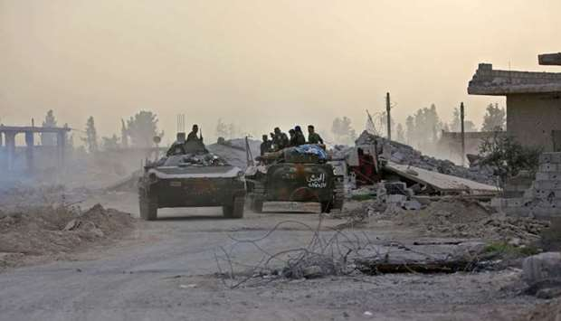 Syrian government forces drive military vehicles in al-Shifoniya as they advance in the rebel-held E