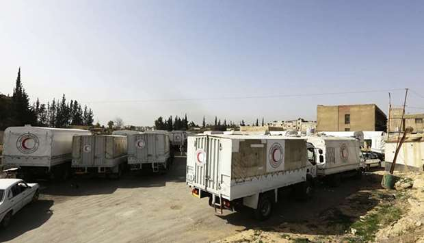 Syrian Arab Red Crescent vehicles carrying aid wait at the al-Wafideen checkpoint on the outskirts o