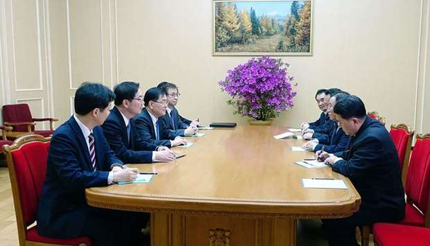 South Korean delegation (L row), who travelled as envoys of the South's President Moon Jae-in, talki