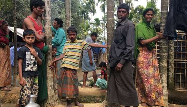 Rohingya Muslims gather outside their makeshift homes on land belonging to Bangladeshi farmer Jorina