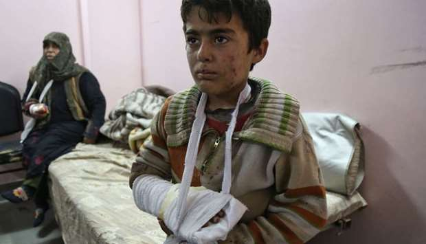 Wounded Syrians wait to receive treatment at a make-shift hospital in Kafr Batna following reported