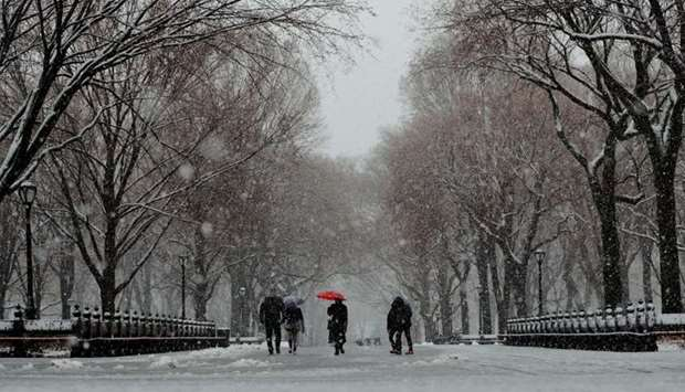 Pedestrians walk through Central Park during a snow storm in New York