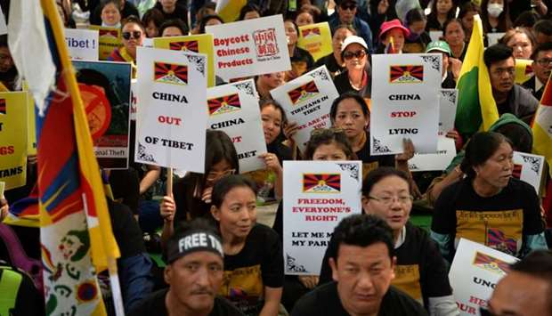 Exiled Tibetan activists hold placards during a protest marking the 60th anniversary of the 1959 Tib