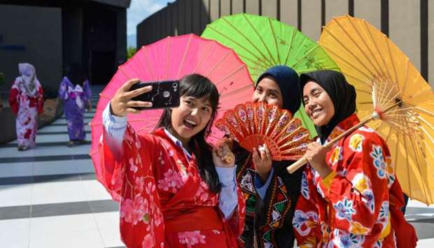Indonesian students dressed in kimonos take selfies as they take part in the remembrance event
