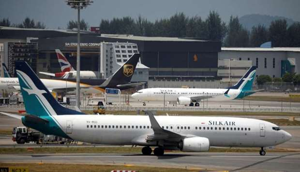 A SilkAir Boeing 737 Max 8 plane (behind) sits on the tarmac near a hangar after suspended operation