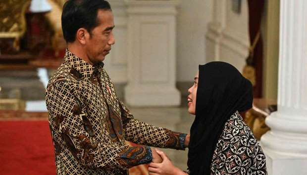 Indonesia's President Joko Widodo (L) welcomes Siti Aisyah (R) during their meeting at palace in Jak
