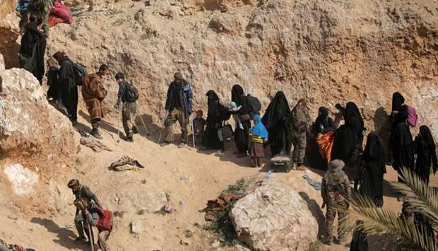 Islamic state fighters and their families walk as they surrendered in the village of Baghouz