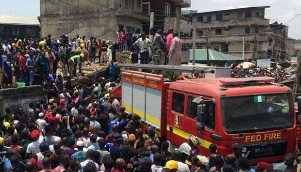 Rescue workers are seen at the site of a collapsed building containing a school in Nigeria's commerc