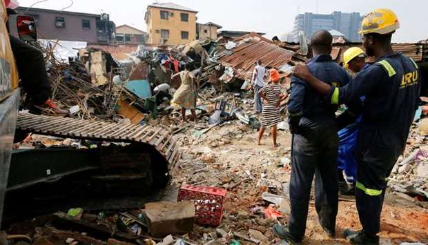 Rescuers are seen as people search for belongings at the site of a collapsed building in Nigeria's c
