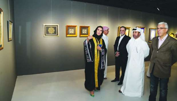 One of the artists briefing Dr al-Sulaiti and other dignitaries about the works on show.