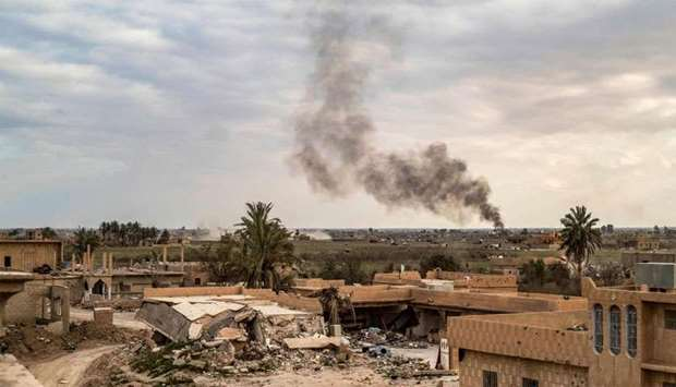Smoke plumes billow from the remains of an Islamic State (IS) militants camp near the village of Bag