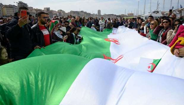 Demonstrators wave an Algerian flag during a protest over fears of plot to prolong the Algerian pres