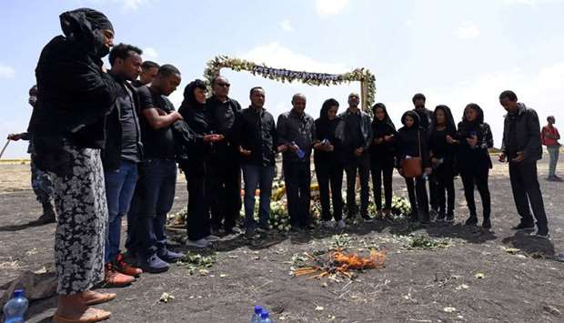 Relatives pay homage to victims near burning candles during a commemoration ceremony at the scene of