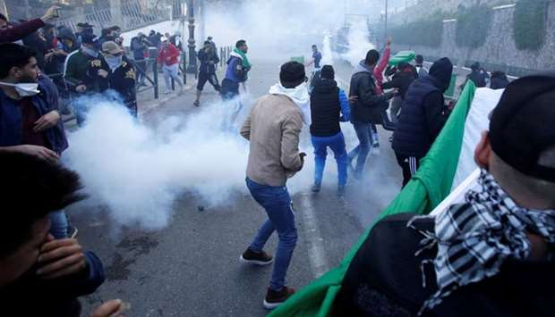 People clash with anti-riot police during a protest against President Abdelaziz Bouteflika's plan to
