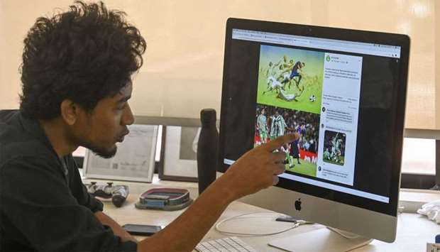 Bangladeshi architect Suhas Nahian, 29, gestures as he shows his painting on his computer at his off