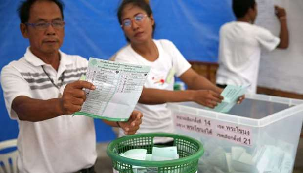 An electoral member shows a ballot during the vote counting, during the general election in Bangkok,