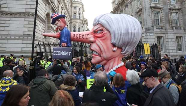 A puppet head of Britain's Prime Minister Theresa May spearing a representation of the British Econo