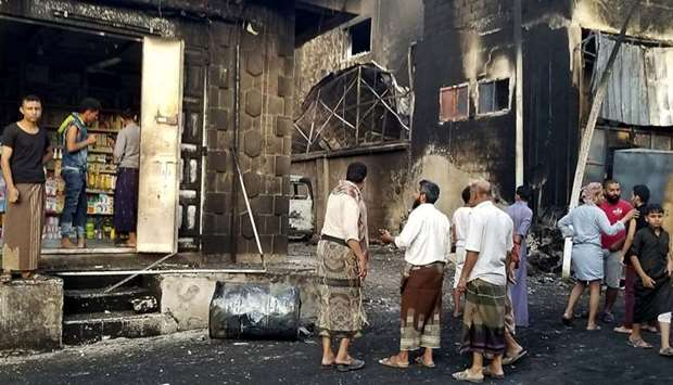 Yemeni men speak in the street by destroyed and burnt buildings in the country's third city of Taez.