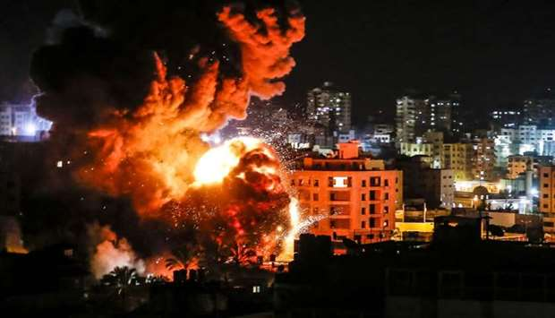 Fire and smoke billow above buildings in Gaza City during reported Israeli strikes