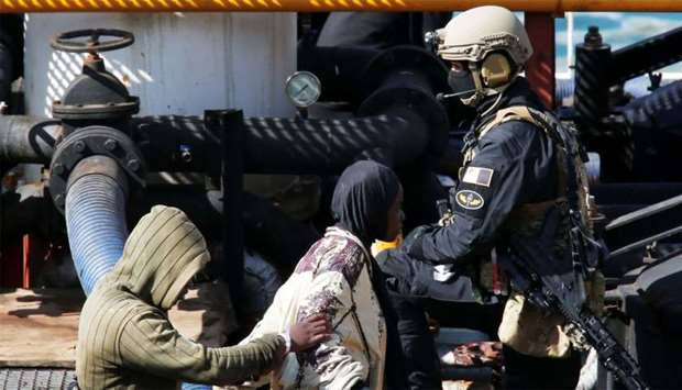A Maltese special forces soldier guards a group of migrants on the merchant ship Elhiblu 1 after it