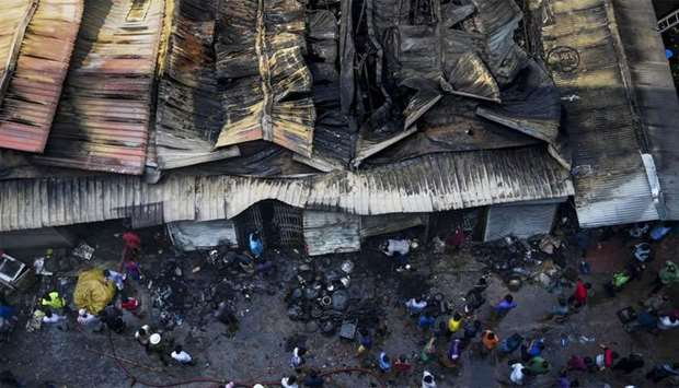 Bangladeshi shop owners gather as they look at their burnt belongings after a fire break out in a ma