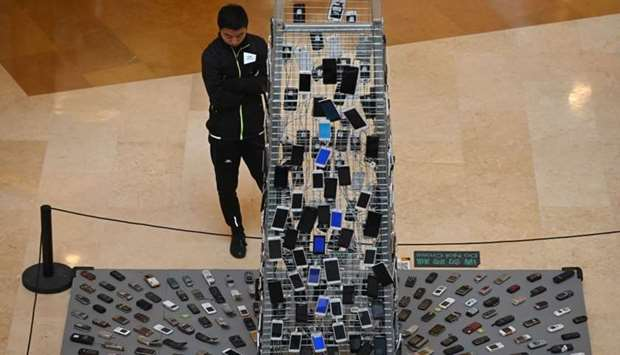 A man looks at an art installation entitled 'Tongtian' by Shen Bolun made from mobile phones at a sh