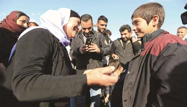 A Yazidi survivor boy is greeted by his relative following his release from Islamic State militants