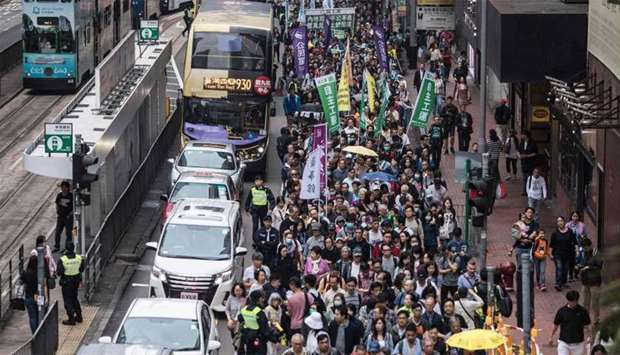 Protesters march along a street during a rally in Hong Kong to protest against the government's plan