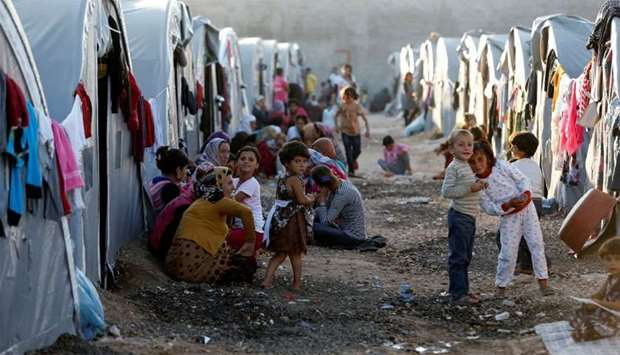 Kurdish refugees from the Syrian town of Kobani sit in front of their tents in a camp in the southea