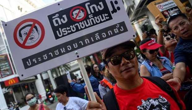 A Thai anti-junta protester displays a placard during a demonstration in Bangkok