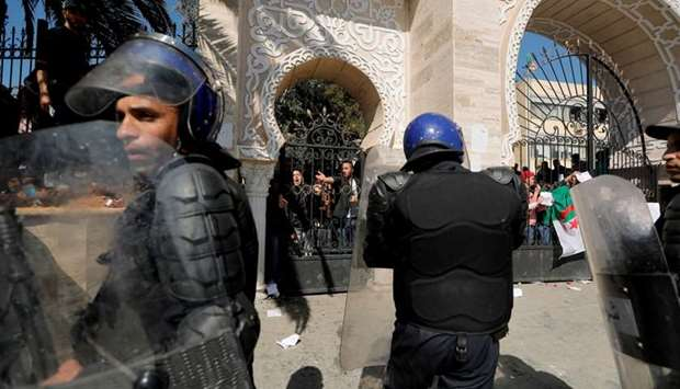 Members of security forces stand guard as students are locked inside the university during their pro