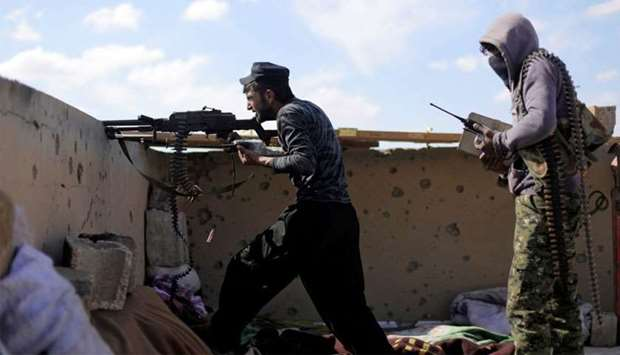 A fighter of Syrian Democratic Forces (SDF) fires a weapon in Baghouz, Deir Al Zor province