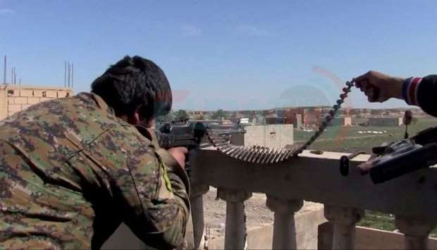 A soldier said to be from US.-backed Syrian Democratic Forces is seen firing a rifle from a rooftop