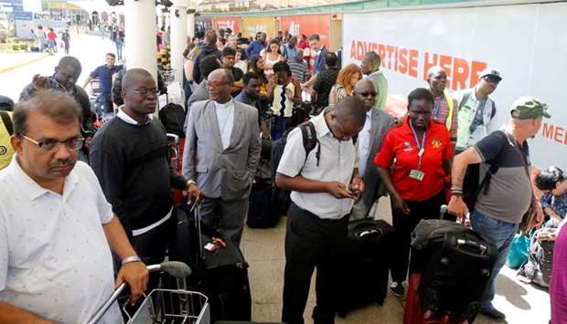 Passengers gather to be screened for check-in at Jomo Kenyatta International Airport during a labour