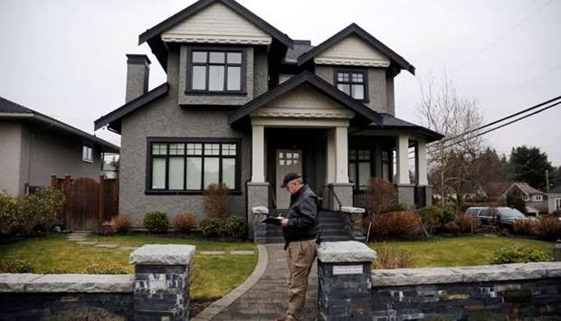 A member of a private security firm stands outside of the family home of Huawei's financial chief Me