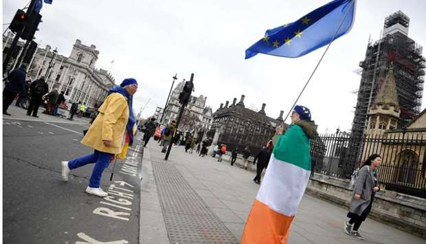 An anti-Brexit protester draped in an Irish tricolour flag and holding an EU flag stands outside of