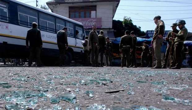Indian police inspect the site of a grenade blast at a bus station in Jammu