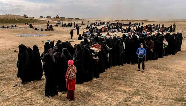 Civilians evacuated from the Islamic State (IS) group's embattled holdout of Baghouz wait at a scree