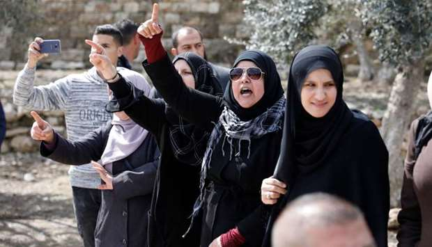 Palestinian women shout slogans, after a group of religious Jews escorted by Israeli security forces