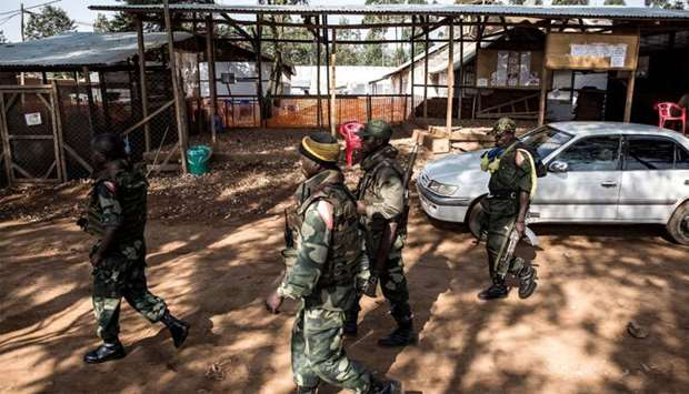 Soldiers from the Armed Forces of the Democratic Republic of the Congo (FARDC) walk outside an Ebola