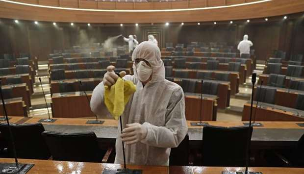 Sanitary workers disinfect the desks and chairs of the Lebanese Parliament in central Beirut
