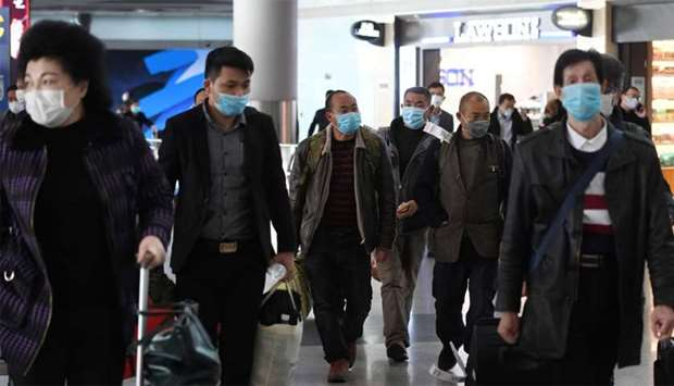Passengers wear face masks as a preventive measure against the COVID-19 coronavirus as they arrive f