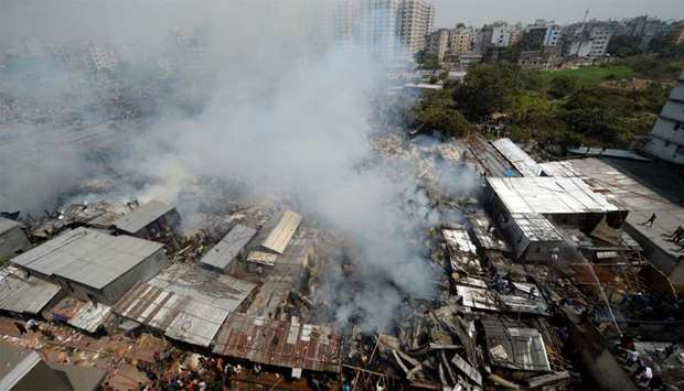 Smoke billows as firefighters work to extinguish a fire at a slum area in Dhaka