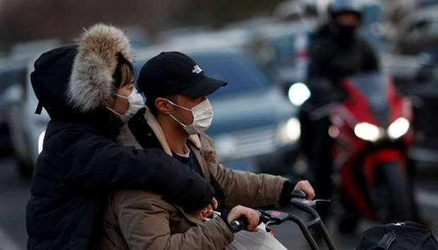 People wear face masks in a street in Beijing as the country is hit by an outbreak of the novel coro