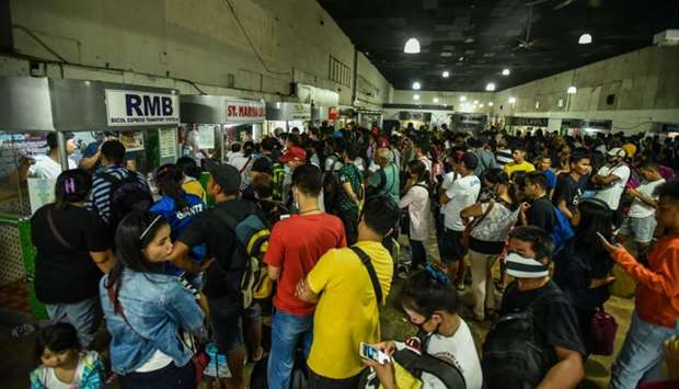 Passengers line up inside the Araneta Center Bus Terminal in Cubao for tickets in Manila yesterday f
