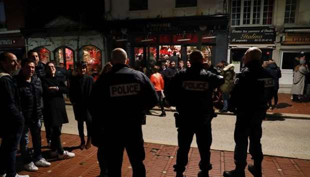 Police officers speak to customers as they control the closure of a cafe at midnight in Le Touquet y