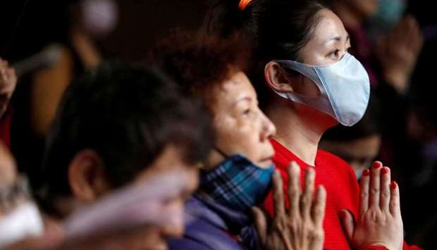Devotees wear protective face masks, to protect themselves from the coronavirus (COVID-19), while pr